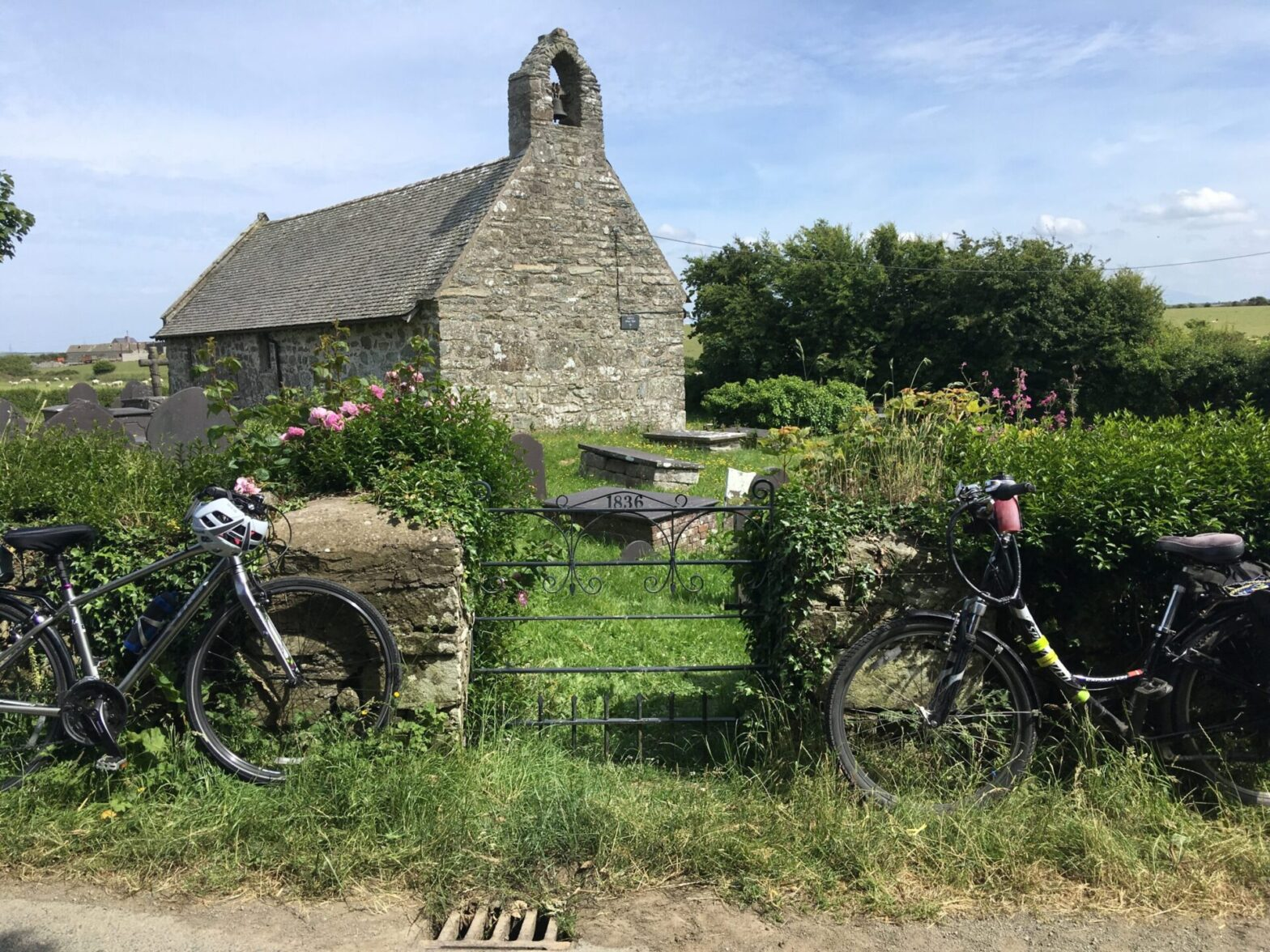 Two bikes rest at gate of Pabo Sant Church, during Off the Beaten Track, Sacred Spaces on Ynys Môn, Anglesey Guided Bike Tour.