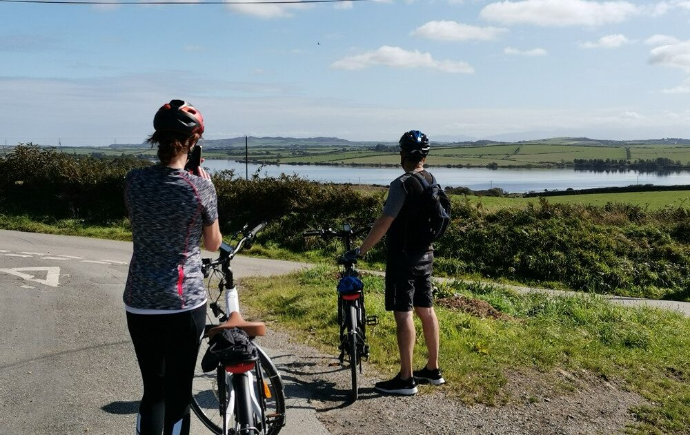 Surveying a view of Llyn Alaw reservoir during Anglesey's Historic Interior Guided Bike Tour