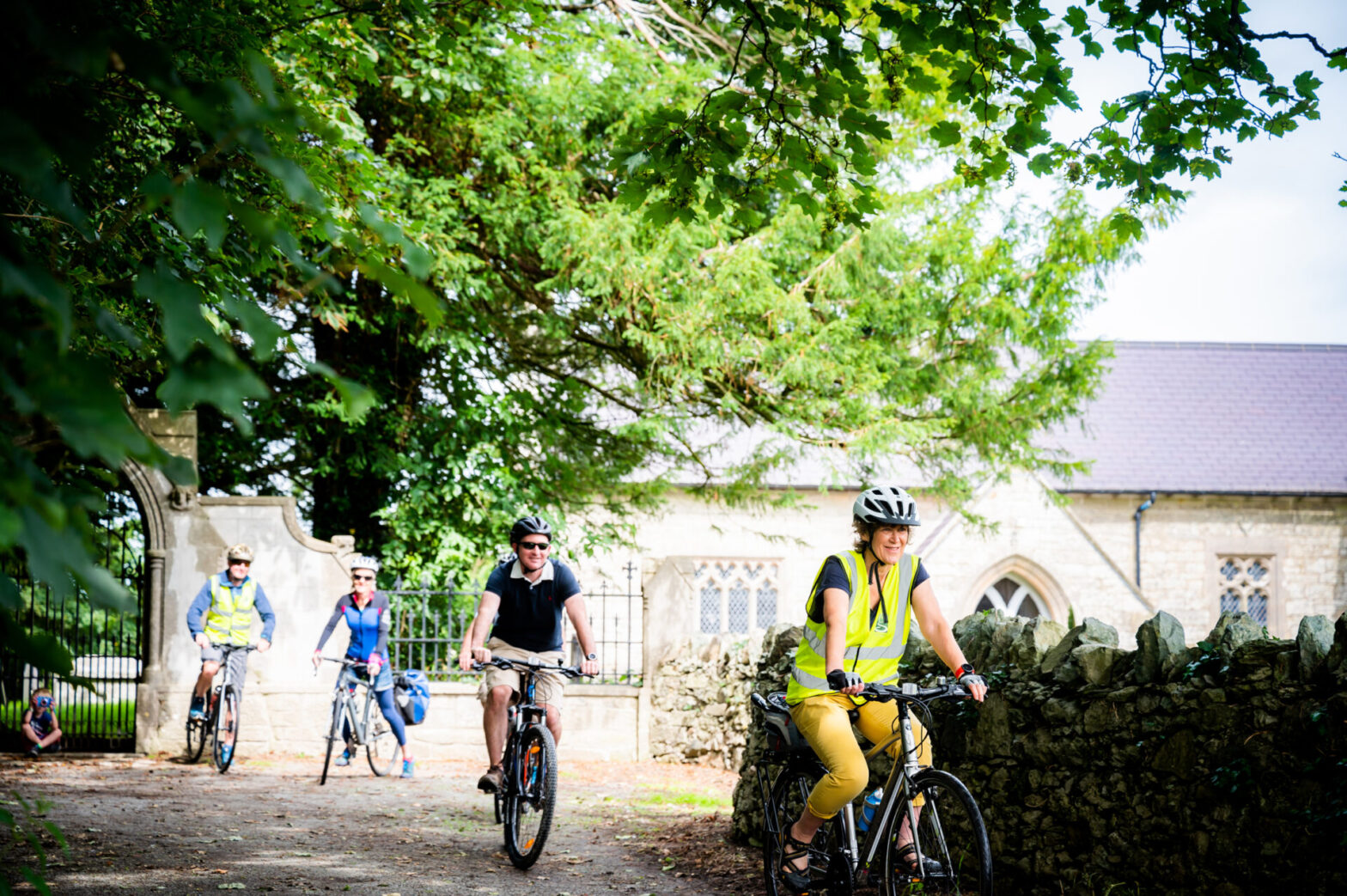 A group of cyclists cycle with a church in the background