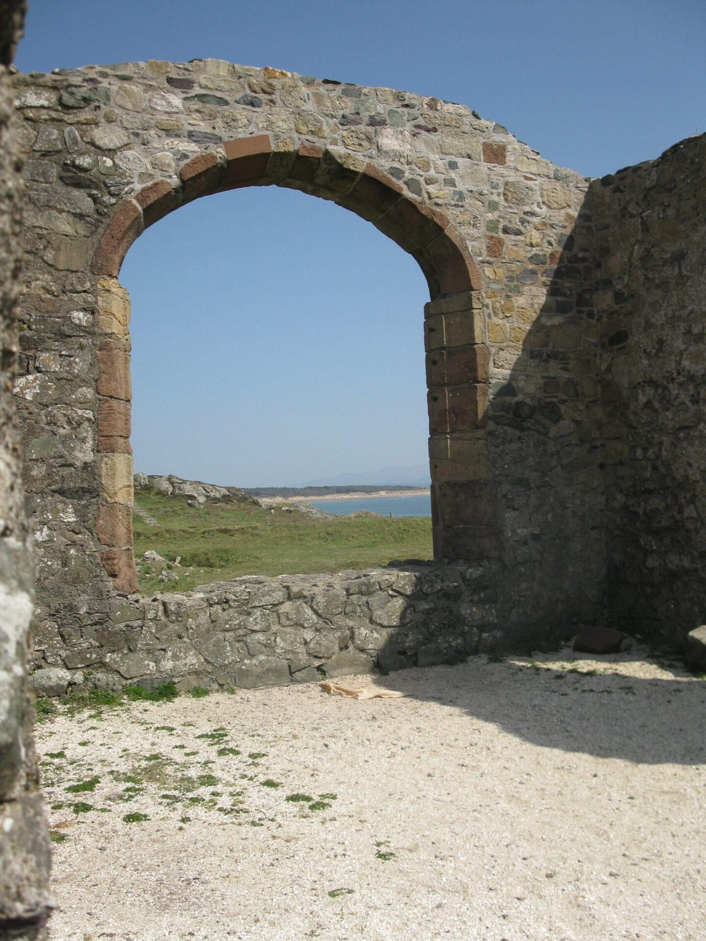 A beach seen through the ruins of a church dedicated to to Dwynwen, patron Saint of Welsh lovers, Ynys Llanddwyn. Island, Anglesey.