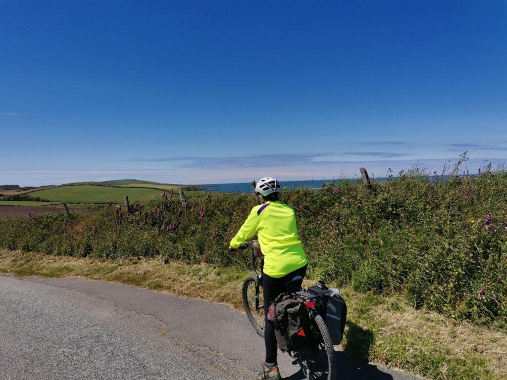 A perso on a bike with a glimpse of blue sea beynd the hedge