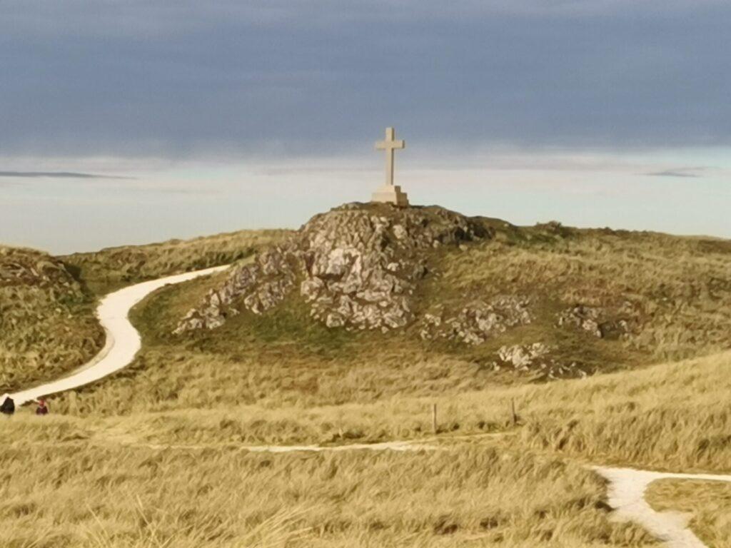 St Dwynwen's cross stands against a blue sky