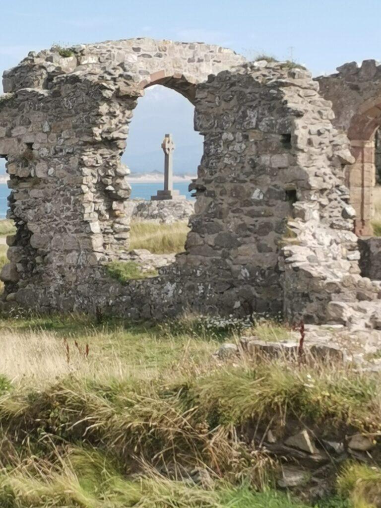 Celtic cross seen through the remains of St Dwynwen's chapel Ynys Llanddwyn